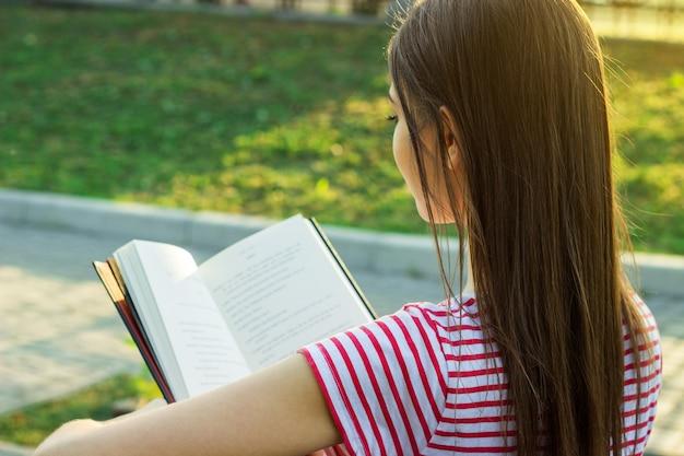 外の本を読んで長く美しい髪の素敵な若い女の子の背面図