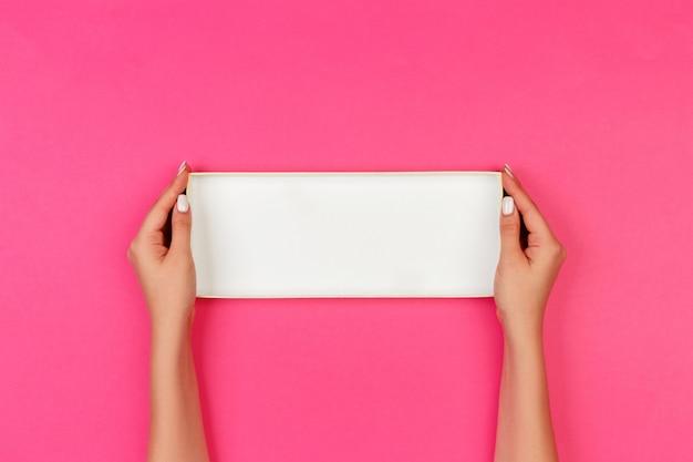 Женщина руки, держа открытую пустую коробку на розовый