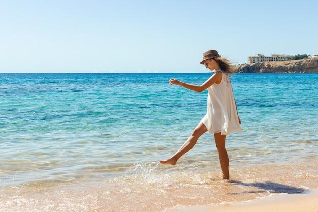 夏の自由を楽しんでいるビーチでリラックスした女性。浜のハップガール