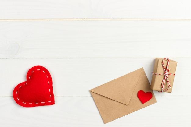 木製の背景に赤いハートとギフトボックス愛の手紙封筒
