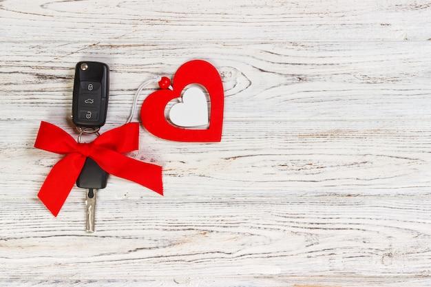 Ключ автомобиля с красной лентой и сердце на белом деревянном столе. дарить подарок или подарок на день святого валентина или рождество