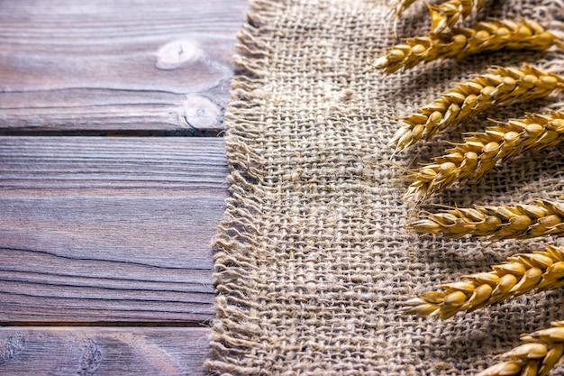 黒の背景テクスチャに小麦の耳、黄麻布の小麦
