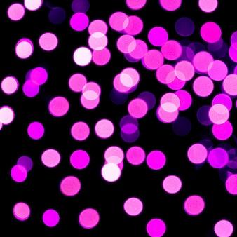 黒い背景にやり場のない抽象的な紫色のボケ味。多重とぼやけた多くの丸い光