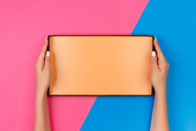 青とピンクの空のボックスを開くと女性の手