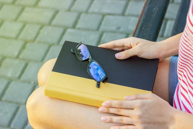 Девушка на скамейке в парке с книгой и очки на коленях. студент читает книгу в парке