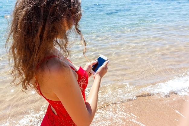 ビーチでスマートフォンで女性のテキストメッセージを閉じます。
