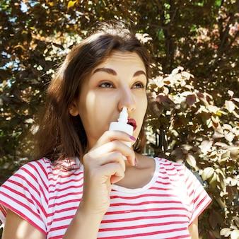 女性が鼻の詰まった鼻に点鼻薬を滴下しています。