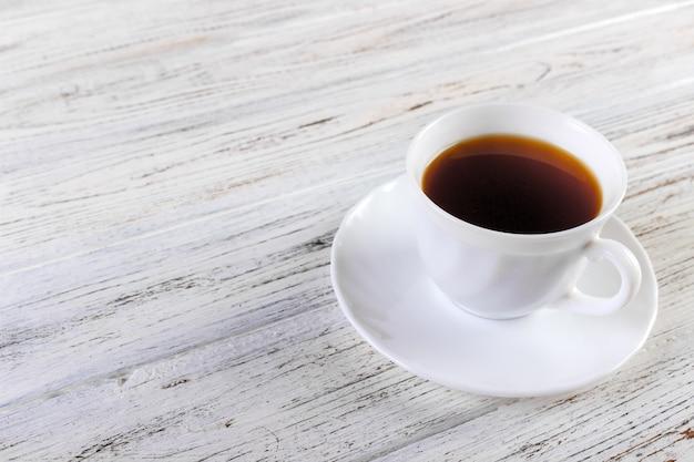Белая кофейная чашка на старом деревянном