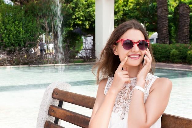 Вскользь счастливая женщина на телефоне в парке сидя на стенде. улыбающаяся девушка разговаривает по телефону