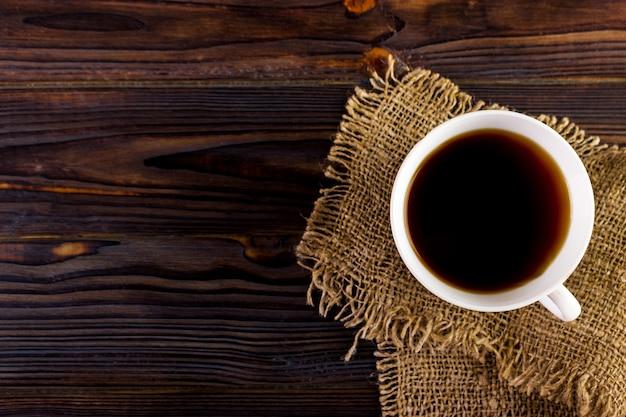 木製のテーブルテクスチャにコーヒーカップ。上からの眺め
