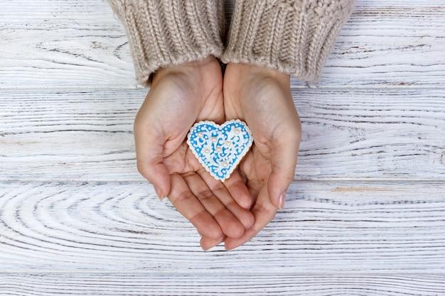 クッキーを保持している女性の手。ホリデークッキー