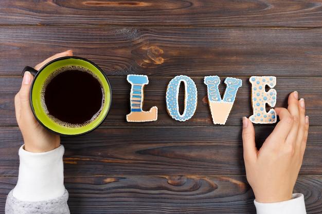 Женские руки с кофе и печенье в форме сердца на деревянный стол