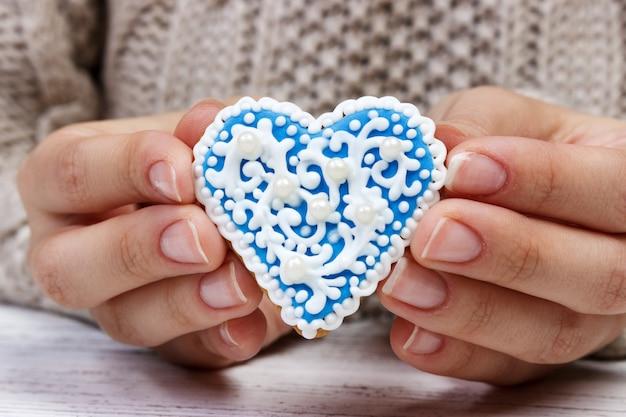 手はハートの形でクッキーを保持する