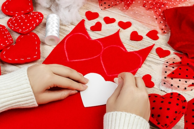 Женские руки делают красные сердечки из ткани. подготовка ко дню святого валентина. домашние праздничные украшения. вид сверху, плоская планировка