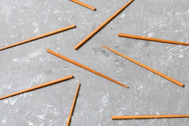 Много бамбуковых палочек на черной предпосылке камня цемента, взгляд сверху с космосом экземпляра. много палочек для суши в виде орнамента