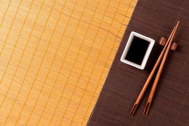 Палочки для еды и миска с соевым соусом на двух бамбуковых циновках и желтым видом сверху с копией пространства