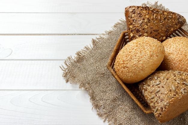 白い木製のテーブルの上のバスケットに新鮮なフランスパン