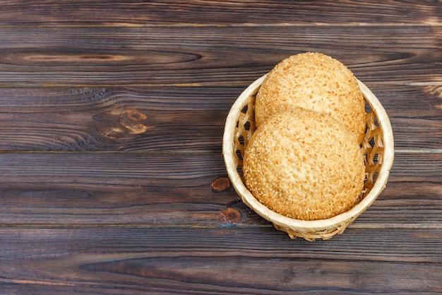 木製の背景にバスケットのパンとおいしいパン