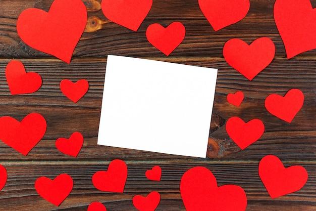白紙のメモ、グランジの木製の背景に赤いハート
