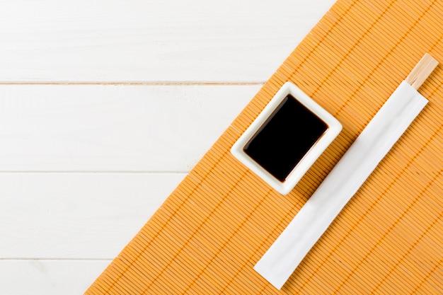 竹マットと白の木製テーブルの上の寿司箸と醤油