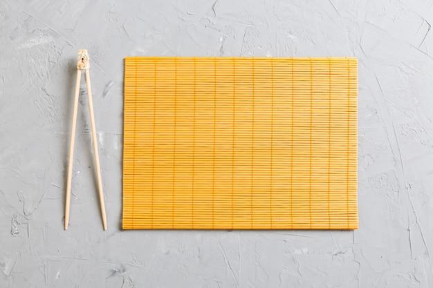 Две палочки для суши с пустым бамбуковым ковриком