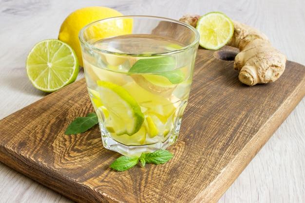 Натуральная имбирная эль-сода в стакане с лимоном и лаймом