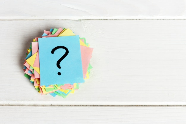 カラフルなクエスチョンマークがリマインダーチケットを書いた質問やビジネスの概念