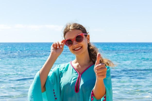 晴れた日に親指をあきらめてビーチで若い女性