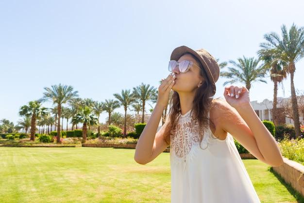 白いロングドレスの女の子は熱帯の手のひらの上を歩いてカメラに空気キスを送ります