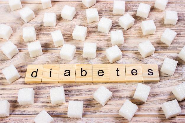 木製の机の上の角砂糖キューブ表面の糖尿病テキスト