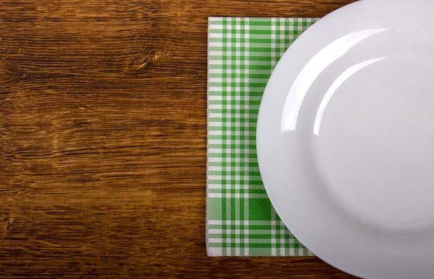 Вид сверху чистой пустой тарелки на деревянной столешнице