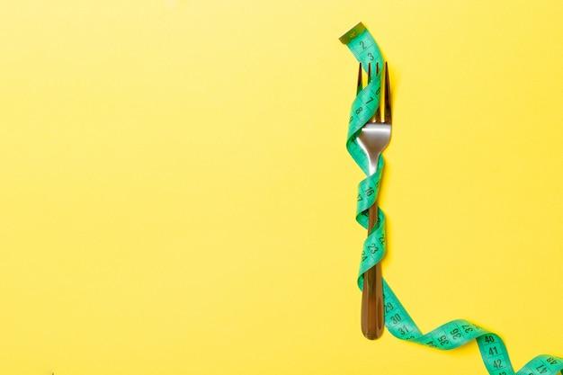 フォークは黄色の測定テープに包まれています