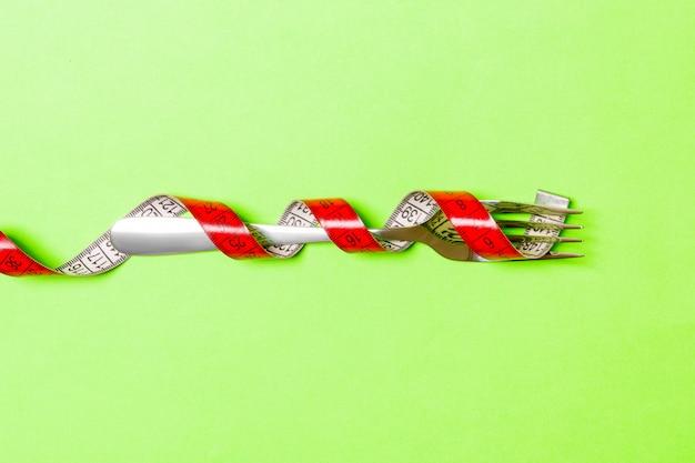 緑の巻尺で包まれたフォークのクローズアップ