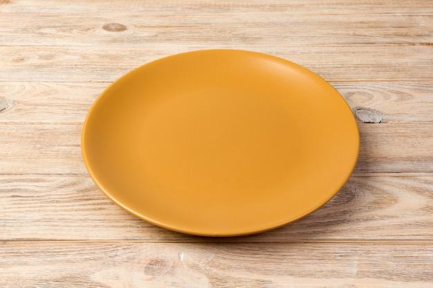 透視図。オレンジ色の木製の背景の空の黄色マットプレート