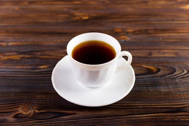 木製の背景にコーヒーカップは、テキストのコピースペースを追加します
