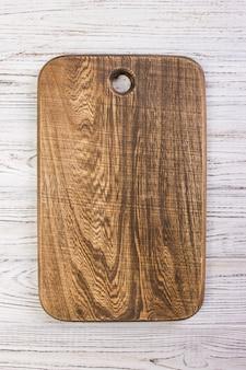 Деревянная доска отбивной на деревенской деревянной столешнице. вид сверху.