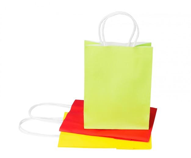 Зеленый пакет из переработанной бумаги стоит на сложенных красных и желтых пакетах