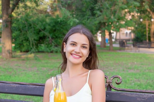 魅力的な若い女性は公園のベンチに座って、ストローでフレッシュジュースのボトルを保持しています。