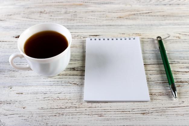 木製の机、平面図、コピースペース上のノートブックとコーヒーのカップ