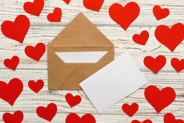 バレンタインデーへの手紙。木製の背景に赤いハートの愛の手紙封筒