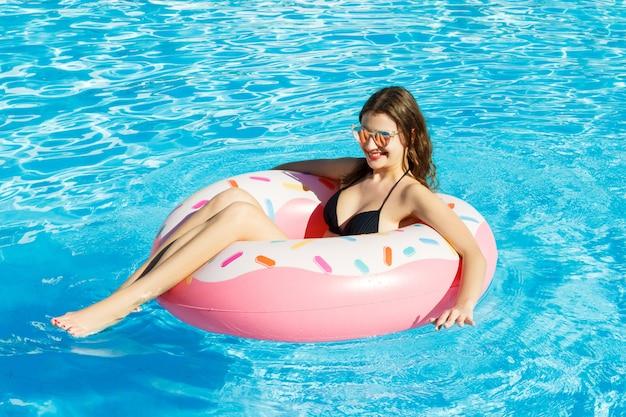 ビキニの若い幸せな女の子はピンクの円でプールで泳いでいます
