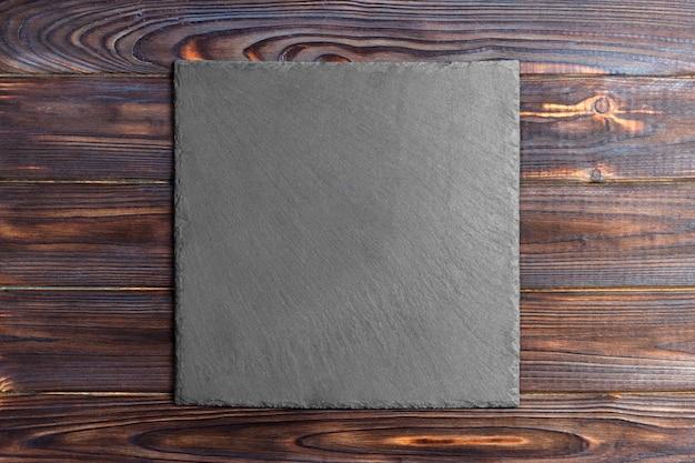 木製の背景に木製のテーブルの上のスレート黒板