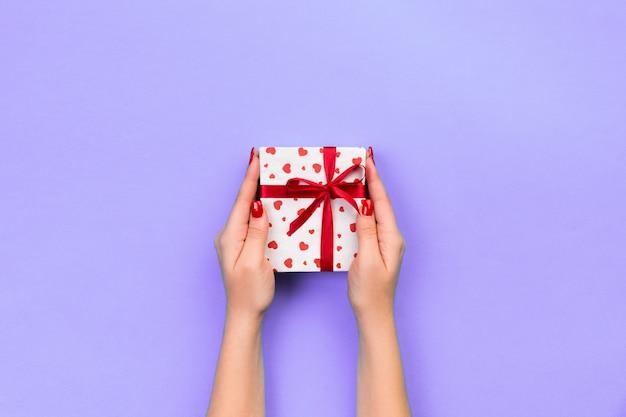 Руки женщины дают завернутые валентина или другой праздник ручной работы в бумаге с красной лентой.