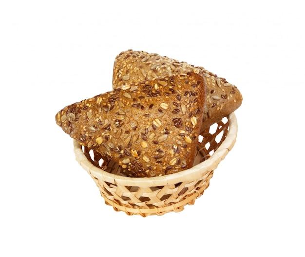 白い背景で隔離のバスケットに亜麻の種子とライ麦パンのクローズアップ