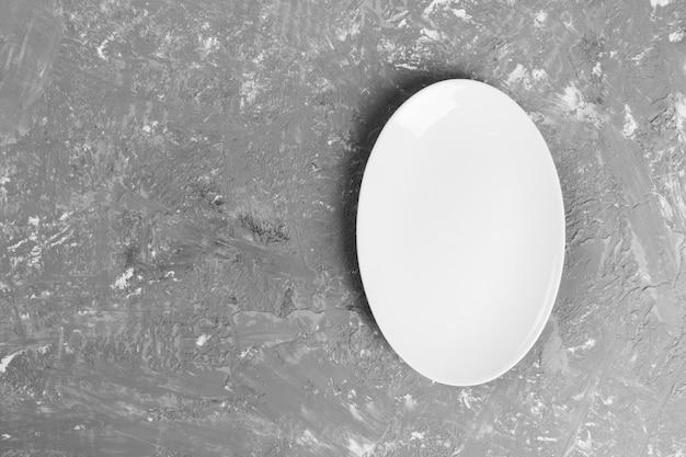 Пустая овальная тарелка на темном текстурированном фоне