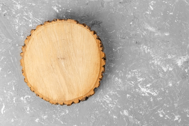 木の切り株ラウンドセメント背景に年輪でカット。コピースペースを持つトップビュー