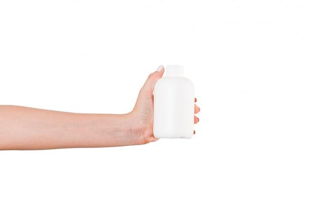 分離されたローションのクリームボトルを持っている女性の手。女の子はチューブ化粧品を与える