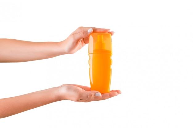 分離されたローションのクリームボトルを持っている女性の手。女の子は化粧品を与える
