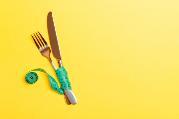黄色の背景に巻尺で包まれたフォークとナイフの平面図です。健康的な食事とダイエットのコンセプト