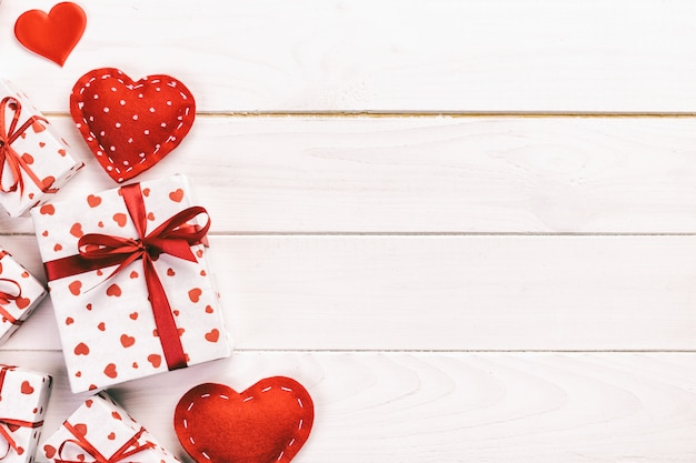 バレンタインや休日のラッパーで赤いハートとギフトボックスと紙で他の休日の手作りプレゼント。コピースペース、デザインのための空のスペースを持つ木製テーブルトップビューにプレゼントボックスギフト